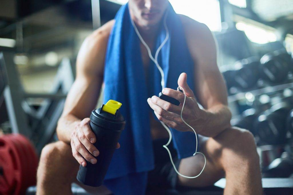 Taking short break from intensive workout: young sporty man listening to music in headphones and holding bottle with water in hand while sitting on bench at modern gym