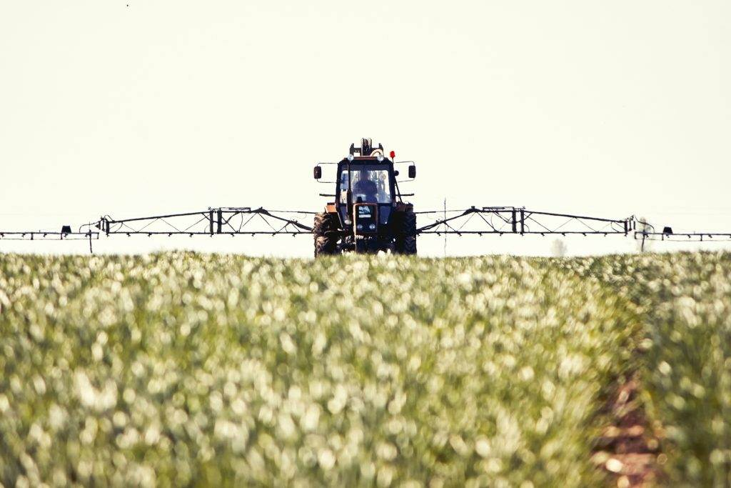 Tractor spraying pesticides on soy bean, spring