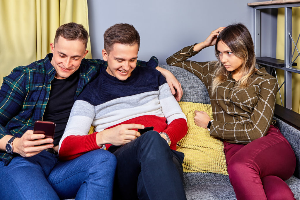 Girl is jealous of her boyfriend to his friend. A woman is watching bromance of guys. Young people portray a homosexual couple to attract the attention of a female. Three students are sitting on couch