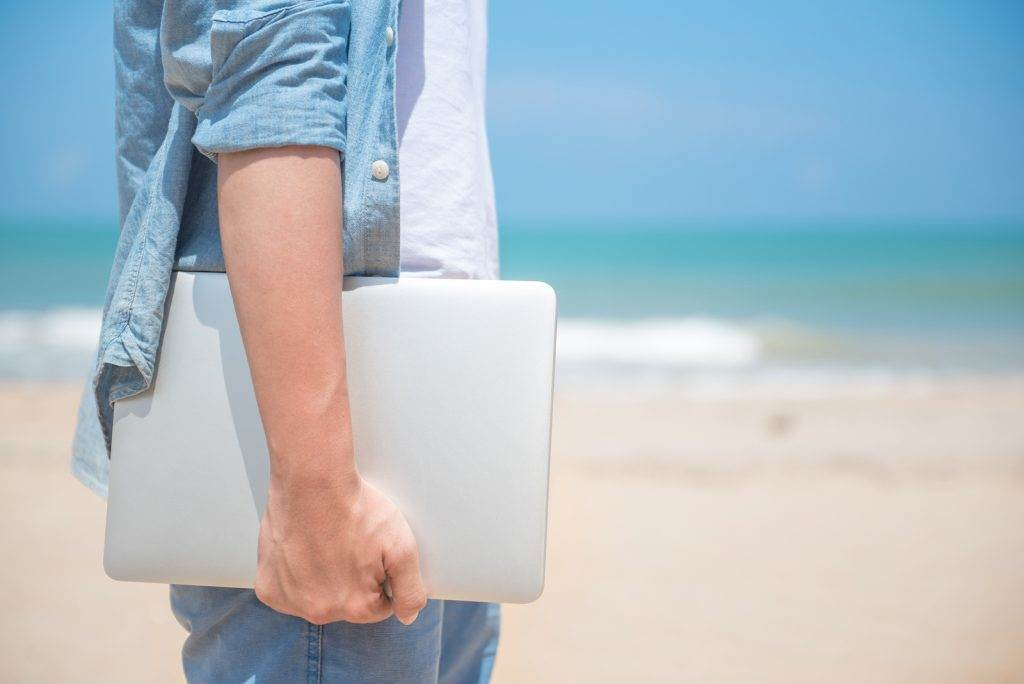 Man hand holding laptop at the beach working outdoor in summer season digital nomad lifestyle concepts