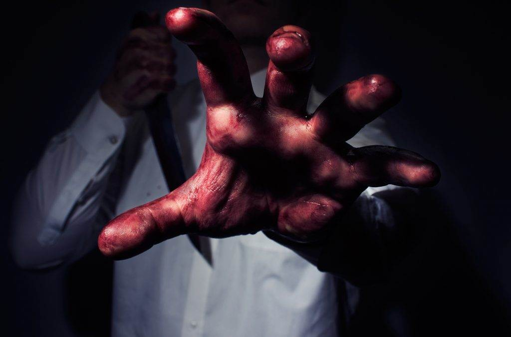 Horror photo of bloody killer with big kitchen knife reaching out a hand to a victim.