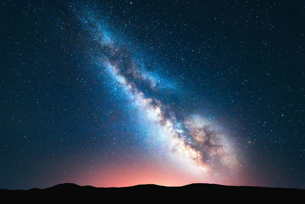 Milky Way. Fantastic night landscape with bright milky way sky full of stars yellow light and hills. Shiny stars. Picturesque scene with our universe. Space background. Amazing astrophotography