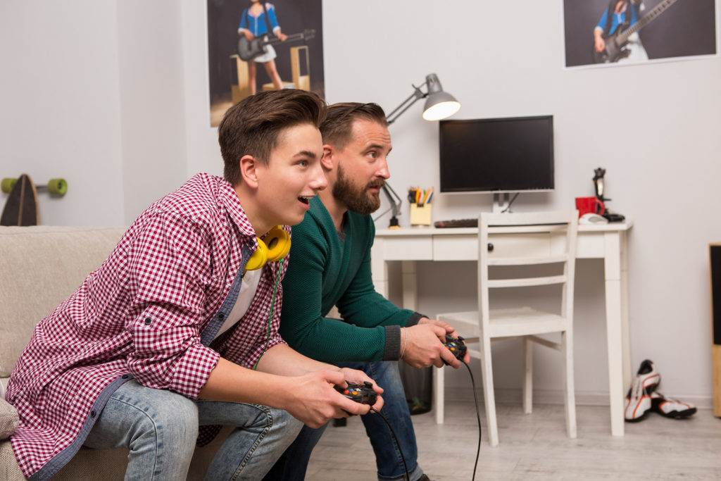 Teenager palying console games with father. Happy time together, dad and young boy excited playing video game.