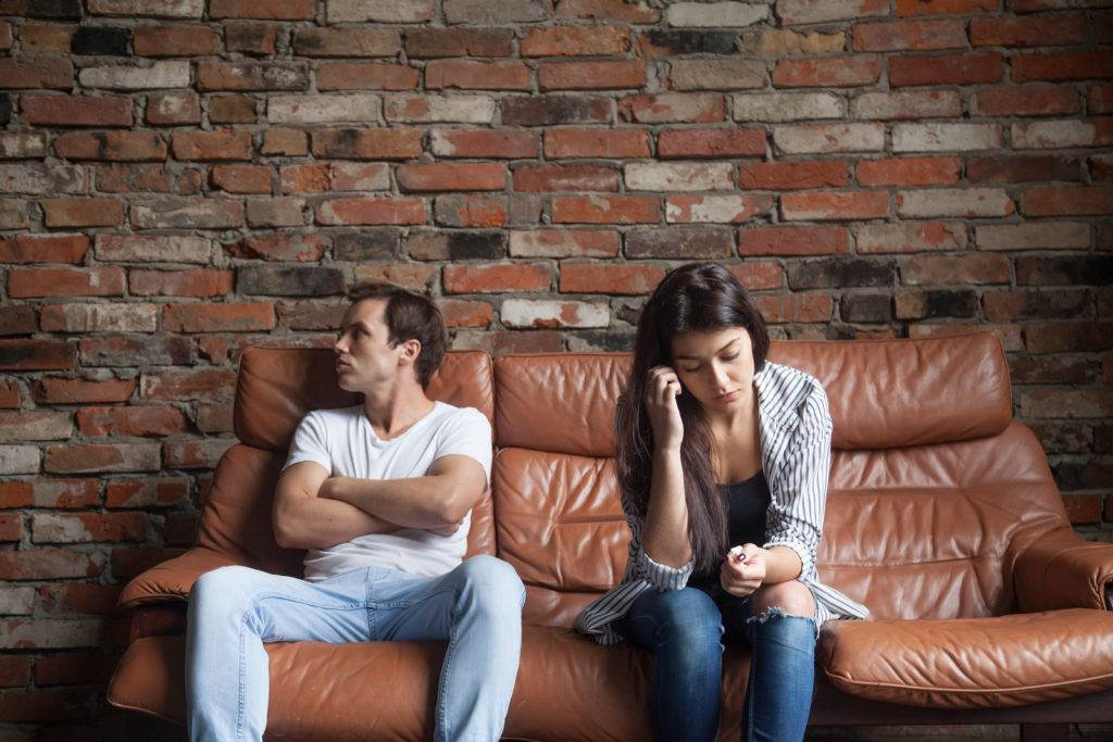 Frustrated upset couple in quarrel not talking after fight, offended stubborn insulted jealous man sitting silent on sofa at home with sad depressed disappointed woman, marriage relationships problem