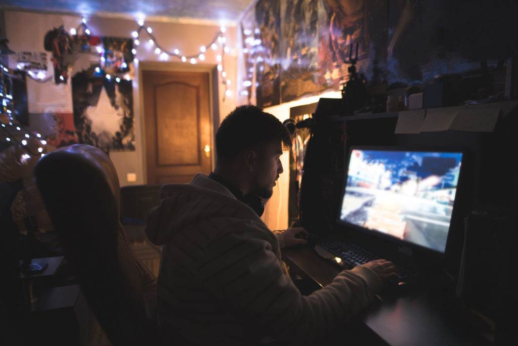 Gamer with Beard plays games on a home computer. A young man sits at home in his room and plays games on a computer. Game of the race on the computer.