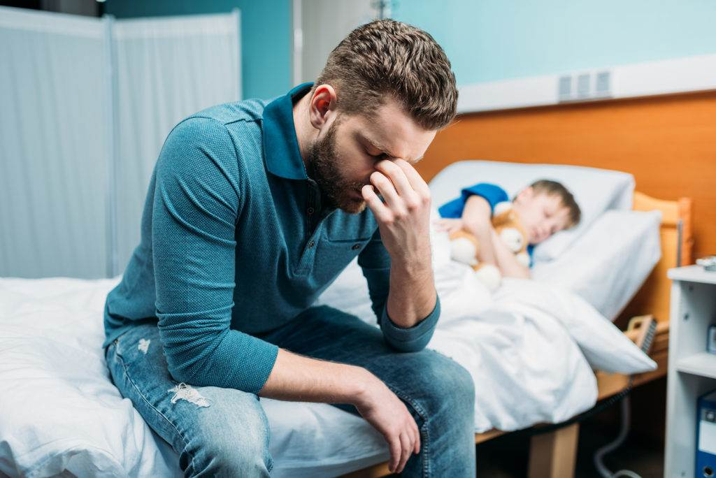 side view of tired dad sitting near sick son in hospital bed
