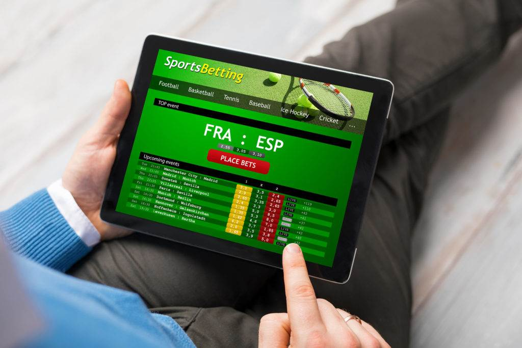 Man using sports betting app on tablet computer