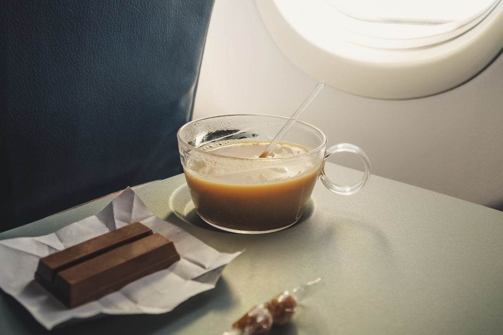 cup with coffee interior of airplane on the background of the plane window on the folding table
