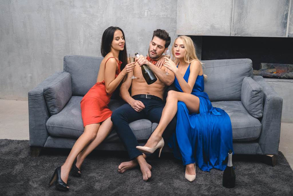 Attractive company have fun and drink at party. Two girl and man drinking alcohol. sex party concept.