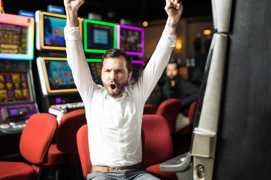 Portrait of an attractive Hispanic man looking very excited about winning some money playing slots in a casino