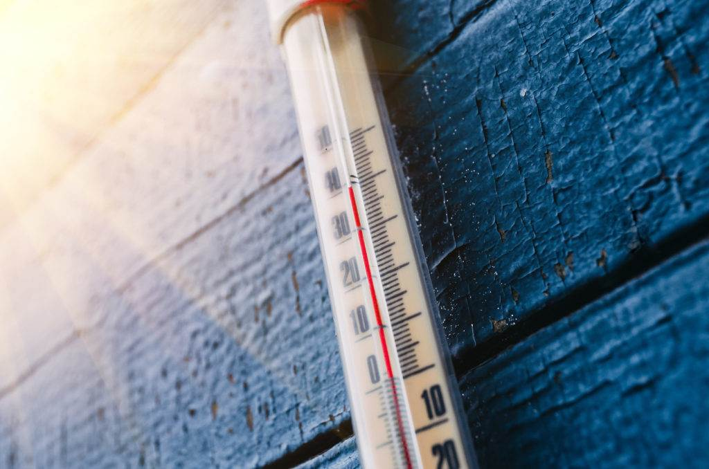 Thermometer on the old wooden wall concept of hot weather