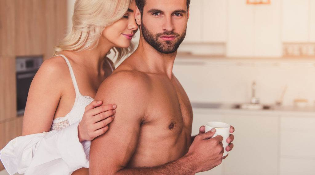 Beautiful young half-naked couple is looking at camera and smiling while hugging in kitchen