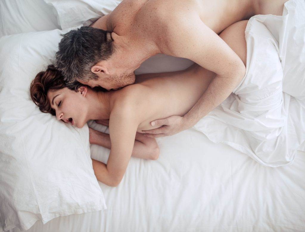 Top view of couple in love having intimate sex in bed. Passionate young couple on bed making love.