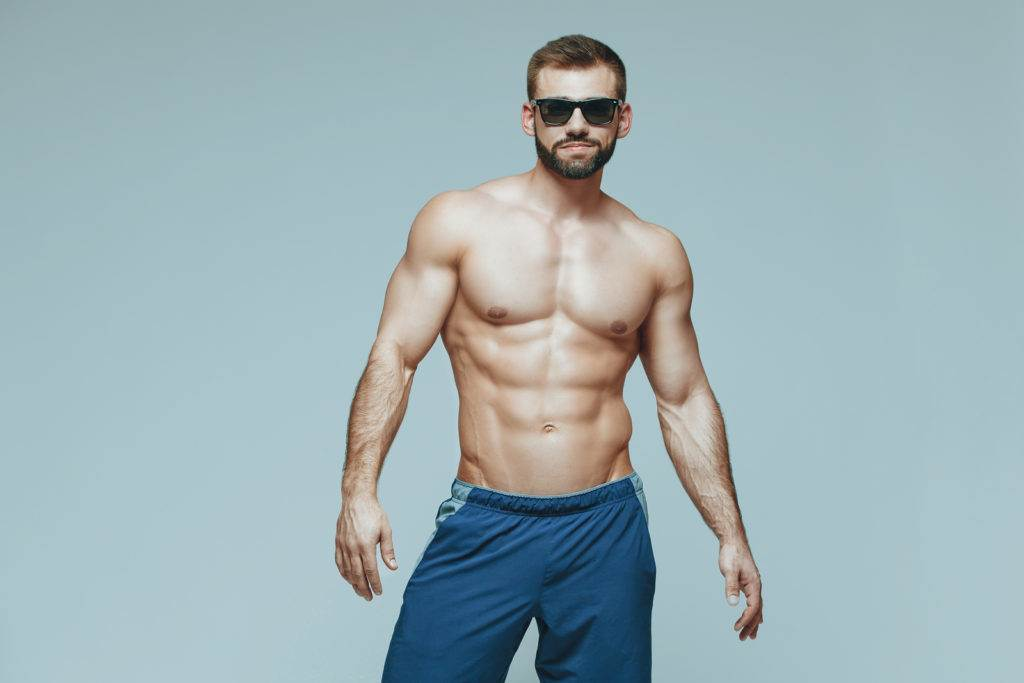 bodybuilder posing. Beautiful sporty guy male power. Fitness muscled in blue shorts and sunglasses. on isolated grey background. Man with muscular torso. Strong Athletic Man Fitness Model Torso showing six pack abs