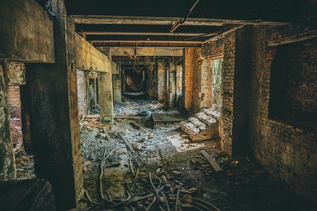 Ruins of industrial building interior after disaster or war or earthquake. Dark creepy tunnel or corridor, horror atmosphere, vintage toned