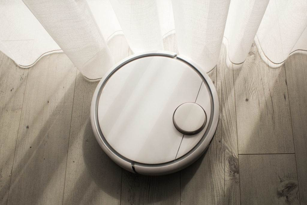 Robotic vacuum cleaner cleans the room from dust and debris, technological progress