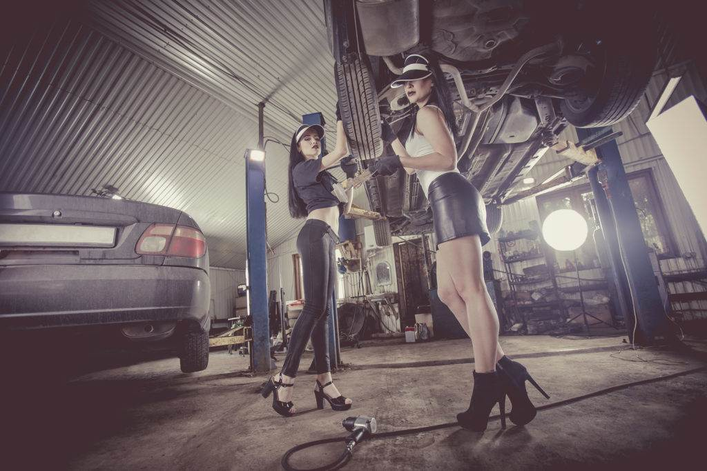Two women mechanics are repairing a car on the lift.
