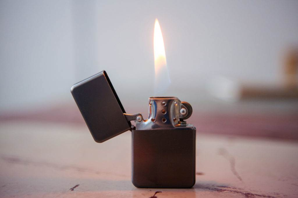 closeup of lighter with flame on wooden table