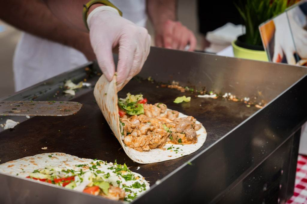 Hands of cook preparing fajita wrap with beef and vegetable salad. Mexican food. Party food. Concept of national food, fresh organic food, recipes and cooking.