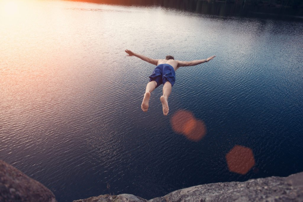 Young man jumping into the water from cliff at sunset with outspread hands