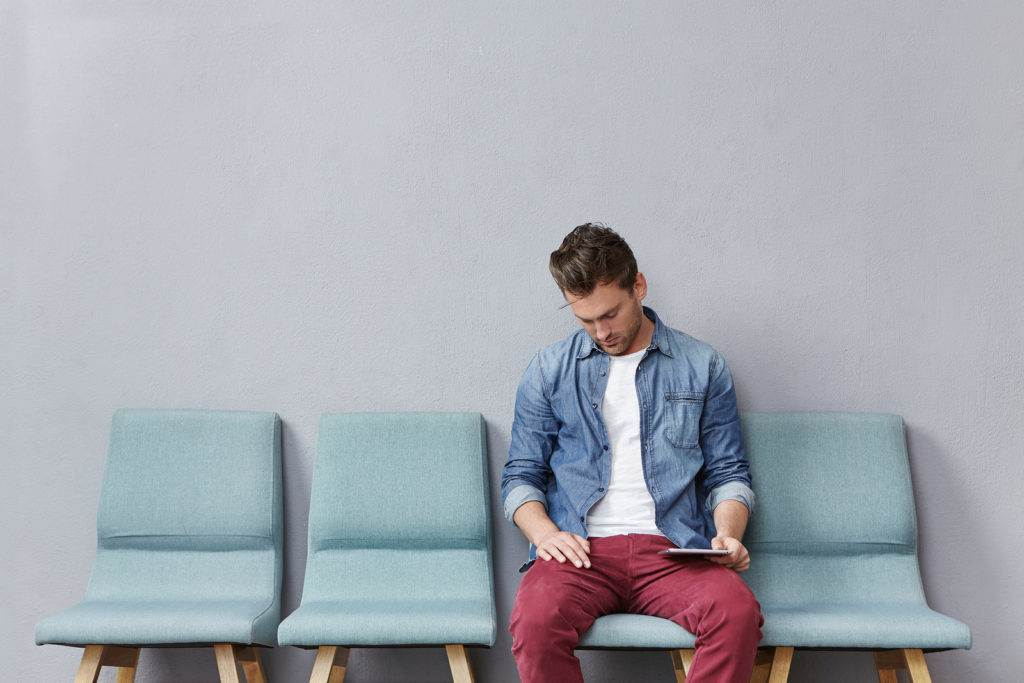 Handsome man in denim jacket and fashionable trousers sits in queue waits for long time his turn feels bored and tired naps on chair with contemporary tablet computer. People waiting concept