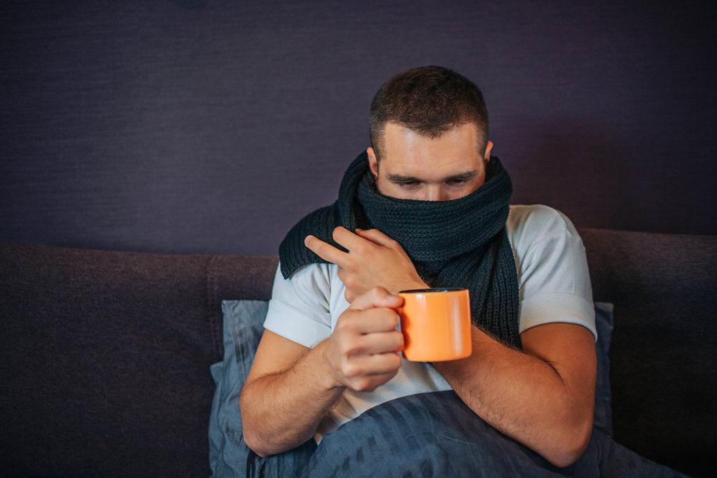 Picture of young sick man sitting on bed and holding orange cup of tea. He looks at it. Guy coveres his mouth with scarf. He got cold.