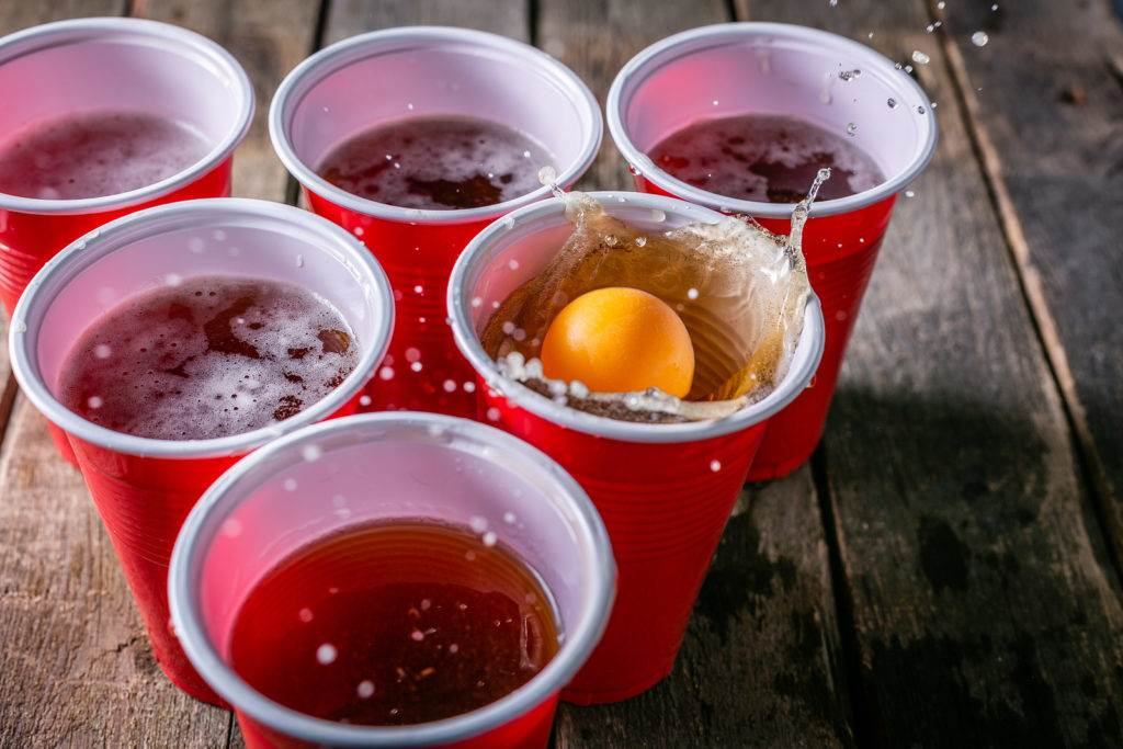 College party sport - beer pong table setting with plastic cups, rustic wood background