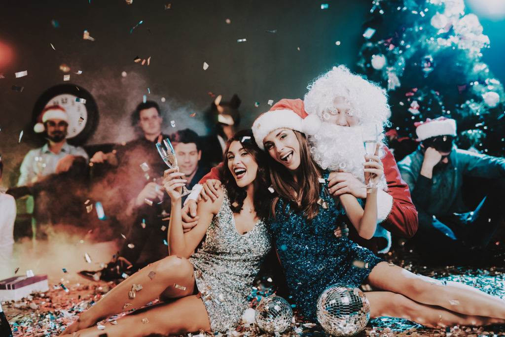 Two Young Women with Santa Claus on New Year Party. Santa Claus Costume. People in Red Caps. Happy New Year Concept. Glass of Champagne. Celebrating of New Year Concept. Young Woman in Dress.
