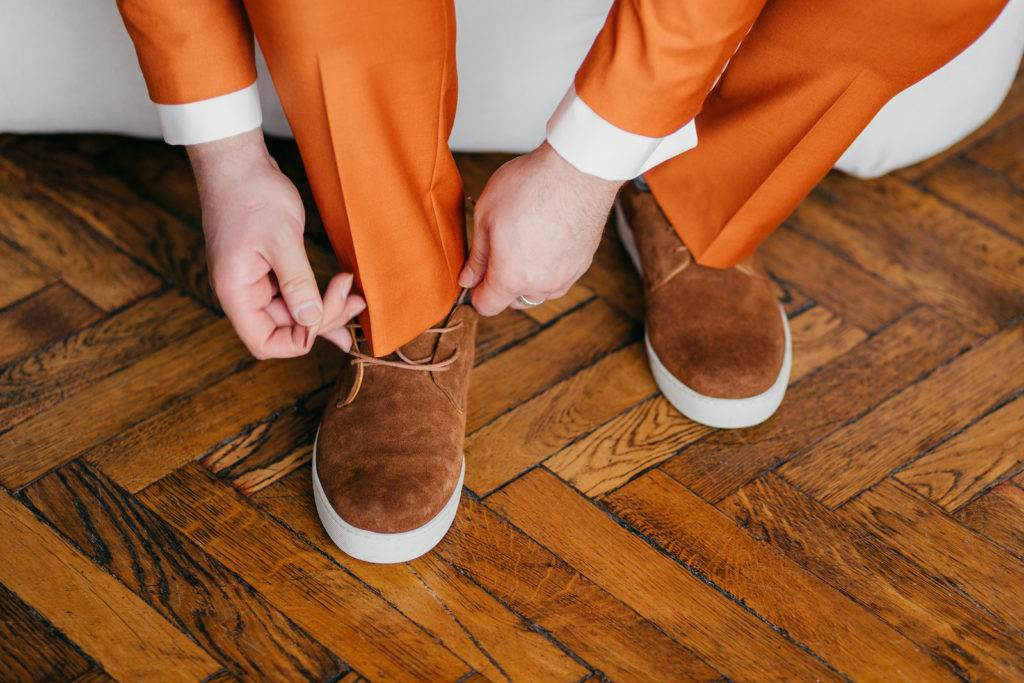 Unrecognizable man in elegant orange suit, laces shoes, prepares for formal meeting or special occasion, poses indoor. People, clothes, design and fashion concept
