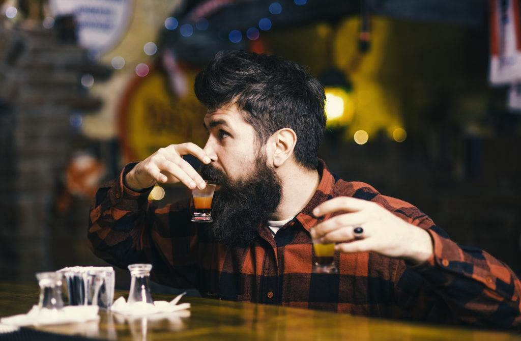 Get drunk concept. Hipster holds glass with alcoholic drink, short cocktail. Guy spend leisure in bar drinking cocktail, defocused background. Man with cheerful face sit alone at bar counter.