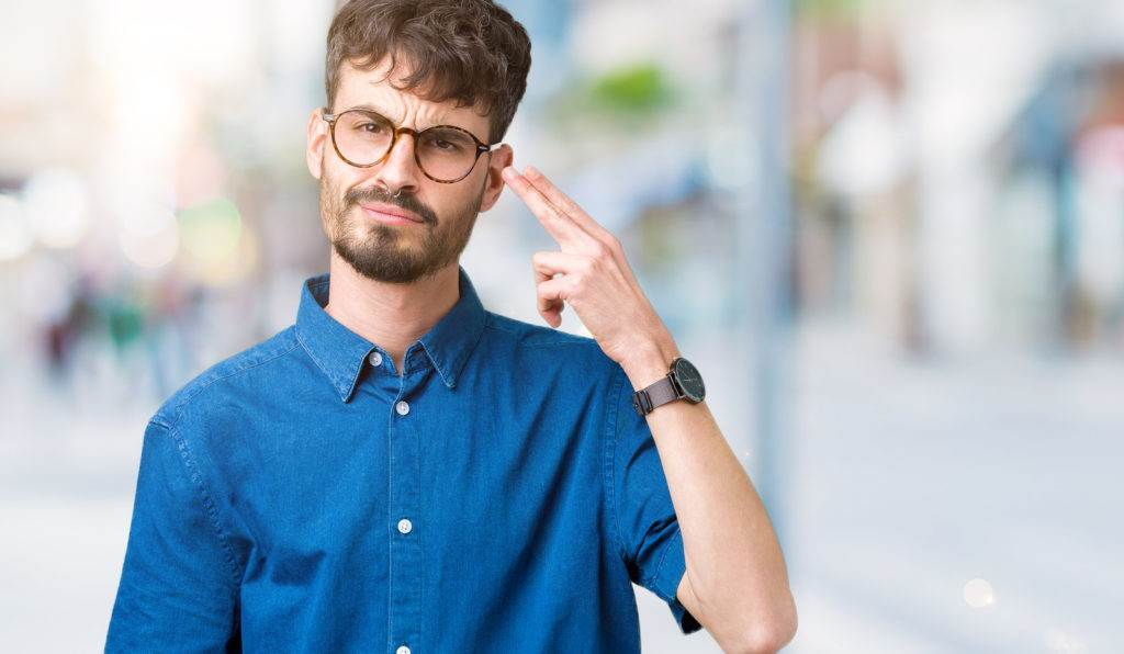 Young handsome man wearing glasses over isolated background Shooting and killing oneself pointing hand and fingers to head, suicide gesture.