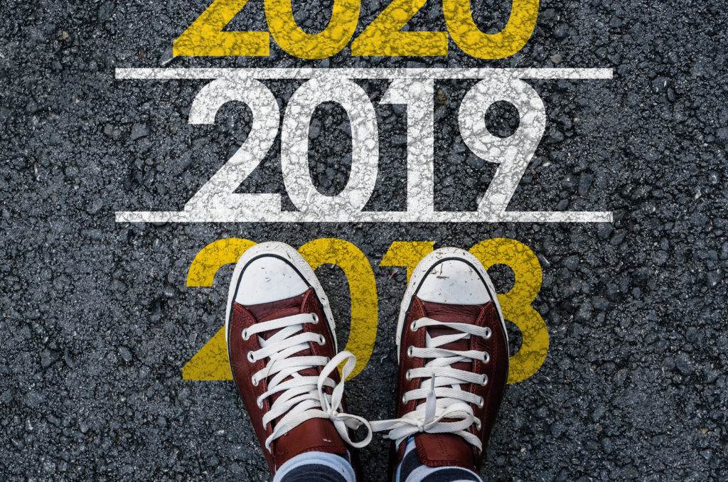 happy new year 2019. man legs in sneakers standing on asphalt road and number 2018 next to number 2019