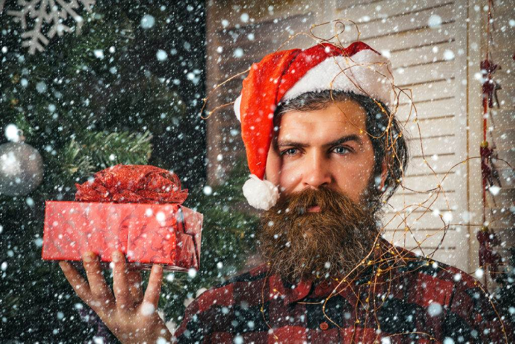 Snew year christmas snow concept santa claus man with present box at christmas tree. Winter holiday and xmas. shopping and party celebration. Christmas man with beard on face hold gift.