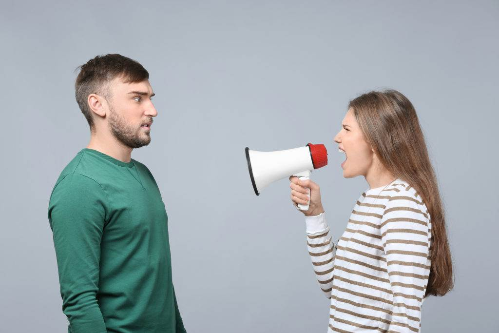 Young woman shouting into megaphone at man on light background. Problems in relationship