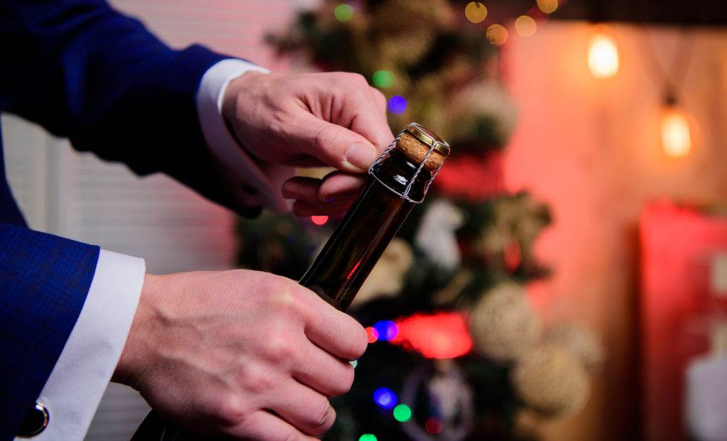 Lets celebrate. Open champagne and celebrate holiday. Celebrate new year with champagne drink. Toast and cheers concept. Male hands opening champagne bottle on christmas decorations background