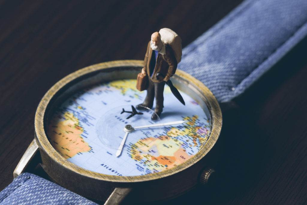 Old man on watches with world map vintage toned photo. World travel banner. Senior traveler figurine. World time zones. Travelling around world concept. Senior age travel. Time of life in vacation