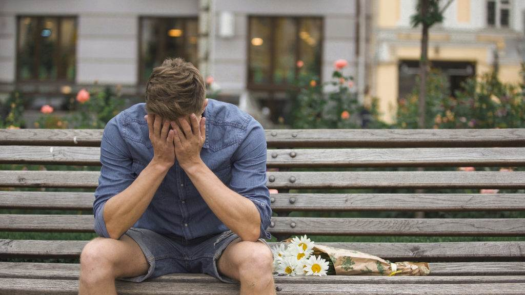 Upset young man sitting on bench alone, closing face with hands, break-up, stock video