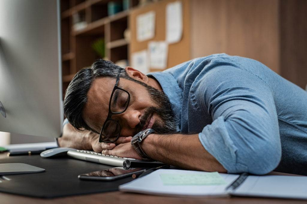 Tired multiethnic businessman sleeping in office. Middle eastern business man with eyeglasses worked late and fell asleep on the computer keyboard. Creative casual man sleeping at his working place