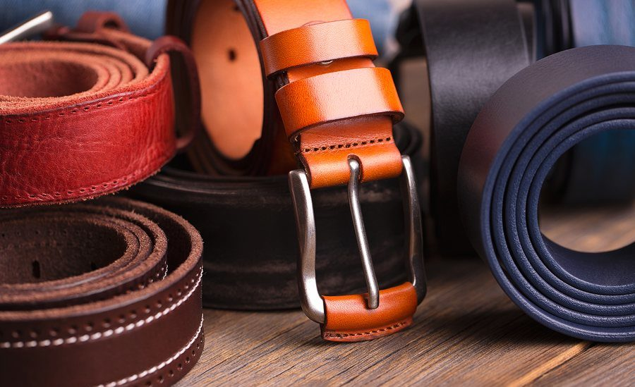 Leather colored belts on a wooden table. Collection of leather belts on a wooden table.